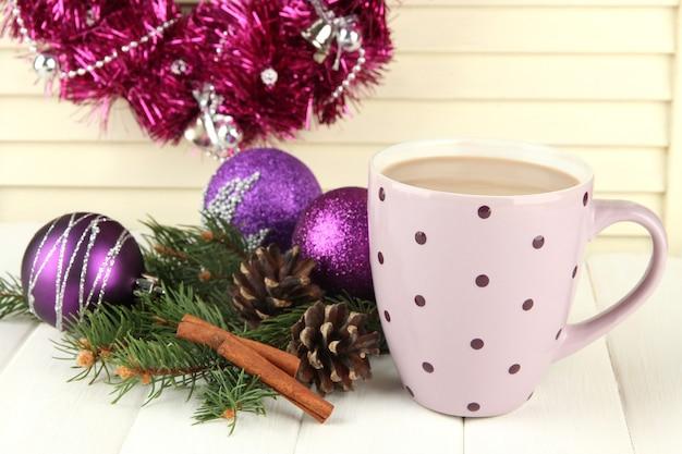 Tasse heißen kakao mit beulen und weihnachtsschmuck auf dem tisch auf holzuntergrund