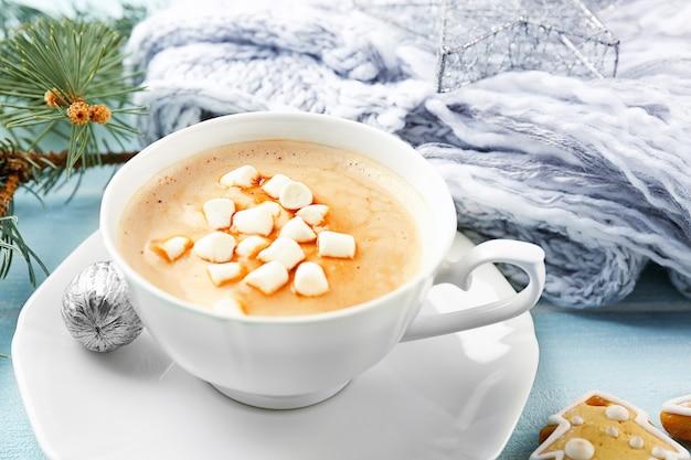 Tasse heißen kakao mit marshmallow, keksen und warmem schal auf blauem tisch