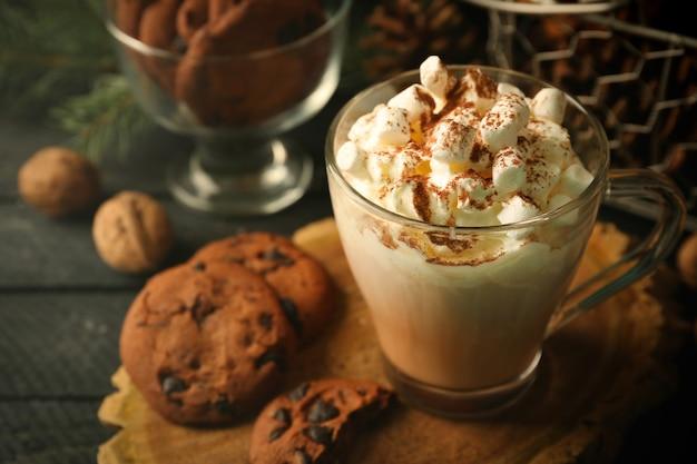 Tasse heißen kakao mit marshmallow und keksen auf schwarzem tisch