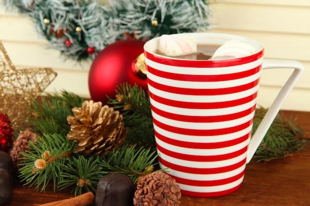 Tasse heißen kakao mit pralinen und weihnachtsschmuck auf dem tisch auf holzuntergrund