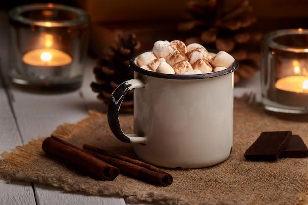 Tasse heißen kakao oder heiße schokolade mit marshmallows und zimtstangen auf hölzernem hintergrund mit brennenden kerzen. rustikal. winterstimmung.