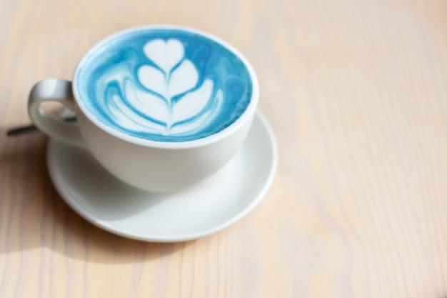 Tasse heißen schmetterlingserbsenlatte oder blauen spirulina latte auf holztisch. bio gesundes und trendiges getränk. konzept für wohlbefinden und entgiftung. speicherplatz kopieren.