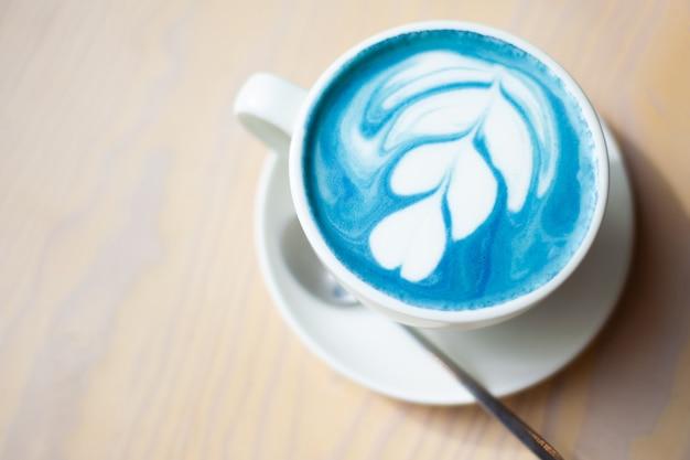 Tasse heißen schmetterlingserbsenlatte oder blauen spirulina latte auf holztisch