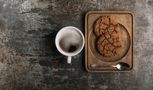 Tasse heißen schwarzen kaffee auf hölzernem schreibtisch mit keksen