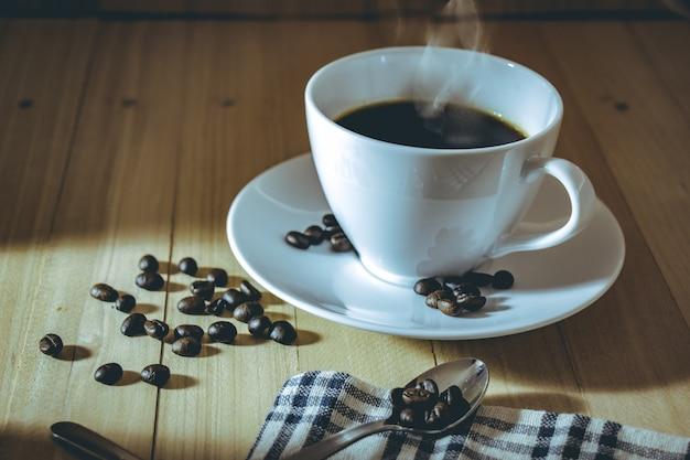 Tasse heißen schwarzen kaffee mit den gerösteten kaffeebohnen