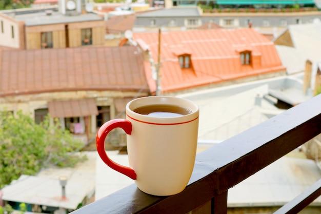 Tasse heißen tee auf der terrasse mit verschwommenem blick auf die stadt im hintergrund