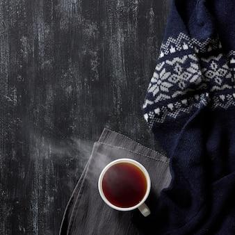 Tasse heißen tee auf einem schwarzen hölzernen hintergrund, warmer winterpullover,