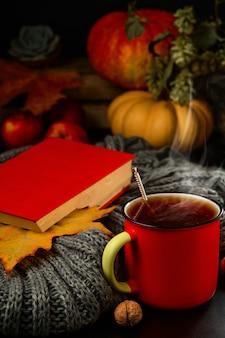 Tasse heißen tee, dampf steigt aus dem getränk. buch, warmer schal und herbstlaub auf dem tisch.