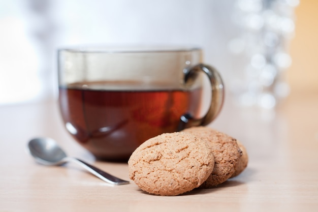 Tasse heißen tee, haferkekse auf einem holztisch. in der nähe eines kleinen löffels.