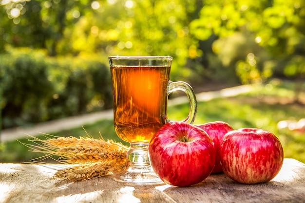 Tasse heißen tee im garten, rote äpfel