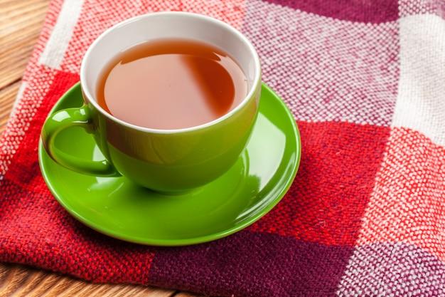 Tasse heißen tee in gestrickten warmen winterschal gekleidet