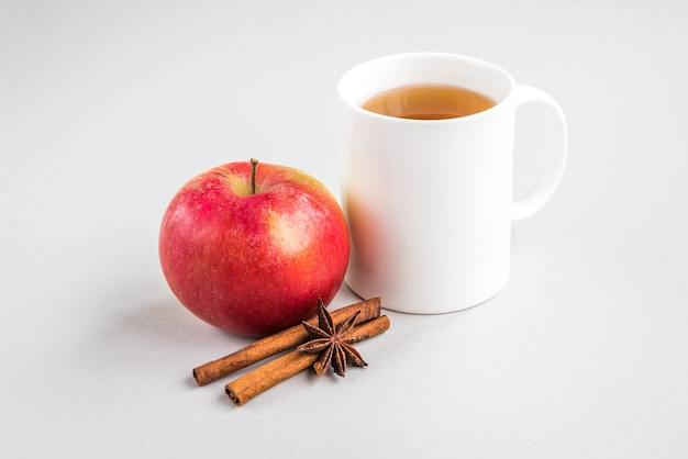 Tasse heißen tee mit apfel und zimt und pillen auf grauer wand. saison grippe. krankheit.