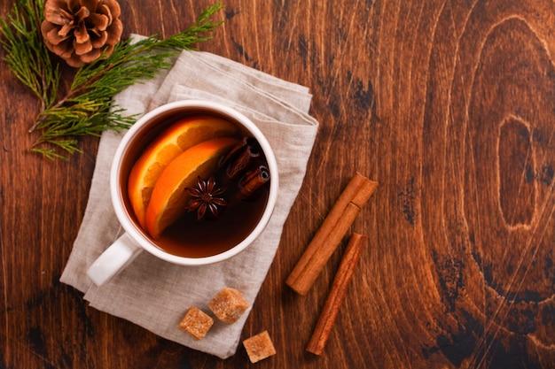 Tasse heißen tee mit orange und gewürzen auf einem rustikalen braunen hintergrund. nahaufnahme