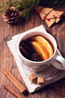 Tasse heißen tee mit orange und gewürzen auf einem rustikalen braunen tisch. nahansicht