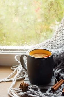 Tasse heißen tee mit zitrone auf der fensterbank wollplaid