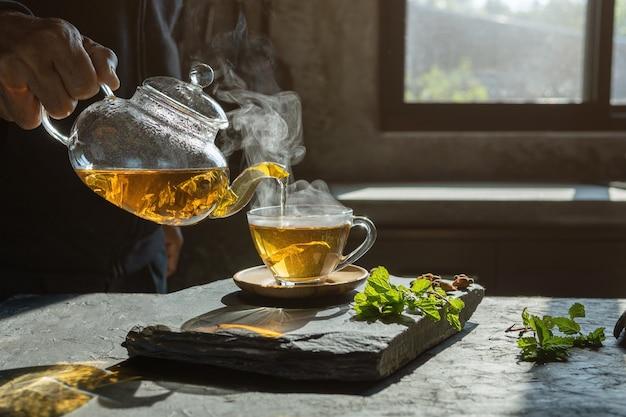Tasse heißen tee trockene teeblätter mit dampf und minzkraut.