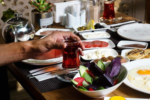 Tasse heißen tee und frühstück auf dem tisch