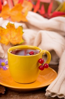 Tasse heißen tee und herbstlaub, auf braunem hintergrund