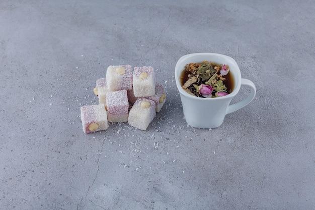 Tasse heißen tee und süße köstlichkeiten mit nüssen auf stein.
