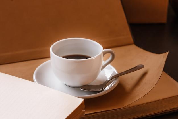 Tasse heißer duftender schwarzer morgenkaffee steht auf einem offenen buch. hellbraune warme farben. selektiver fokus.