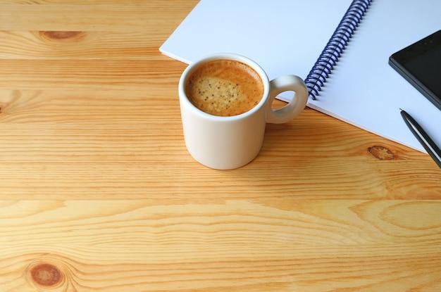 Tasse heißer kaffee mit einem notizbuch und einem mobiltelefon auf hölzernem arbeitsschreibtisch, freier raum für des