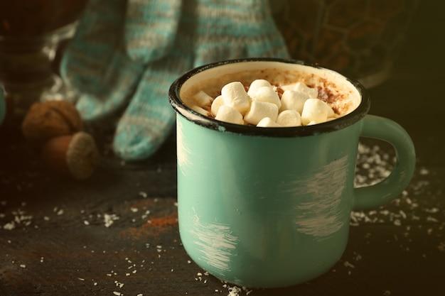 Tasse heißer kakao mit marshmallow und handschuhen auf schwarzem tisch