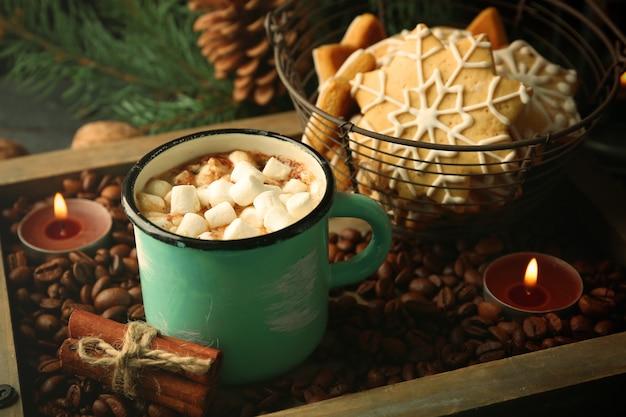 Tasse heißer kakao mit marshmallow und keksen auf kaffeebohnen