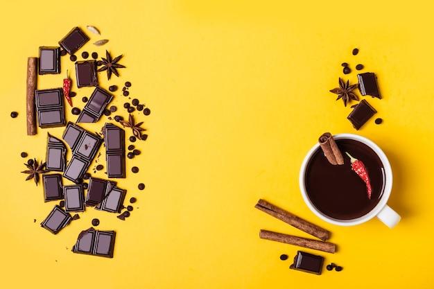 Tasse heißer schokolade mit paprika und zimt. zutaten für das kochen auf gelbem hintergrund. wärmendes winter- oder herbstgetränkkonzept.