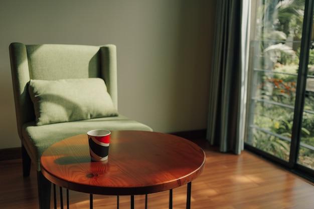 Tasse heißes getränk auf dem tisch mit grünem stuhl in einer klassischen gemütlichen bar.