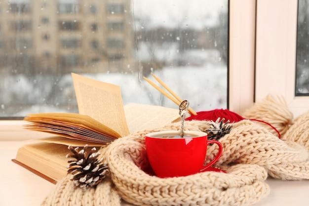 Tasse heißes getränk auf der fensterbank im wohnzimmer. bequemes winterwochenende oder ferien zu hause