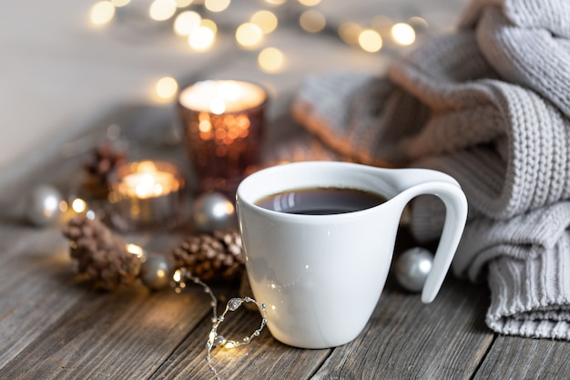 Tasse heißes getränk auf unscharfem hintergrund mit kerzen und bokeh-lichtern
