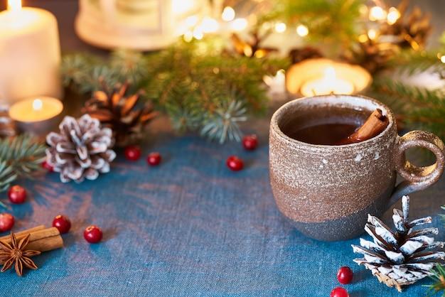 Tasse heißes getränk auf weihnachtshintergrund. gemütlicher abend, becher glühwein