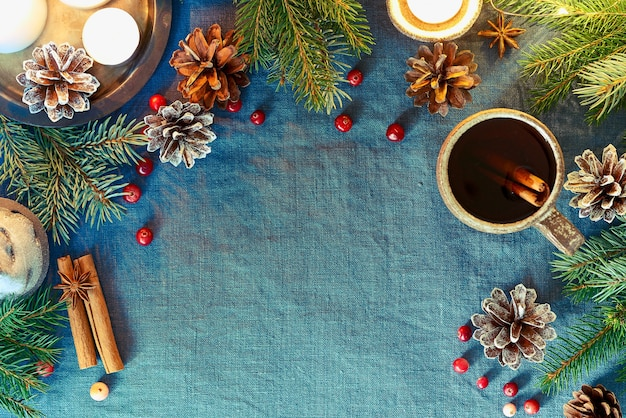 Tasse heißes getränk auf weihnachtshintergrund. gemütlicher abend, eine tasse glühwein, weihnachtsdekorationen, kerzen und lichtgirlanden.