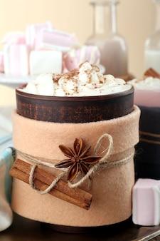 Tasse heißes getränk in filz auf holztisch dekoriert