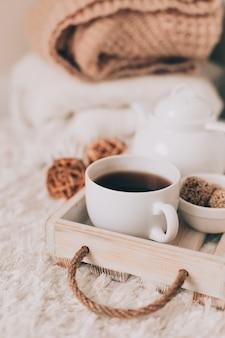 Tasse heißes getränk und teekanne auf einem serviertablett, strickkleidung