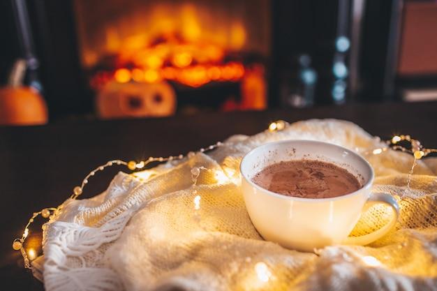 Tasse heißes getränk vor dem warmen kamin. feiertag weihnachten. weißer becher, der nahen kamin steht. gemütliche entspannte magische atmosphäre in einem chalet.