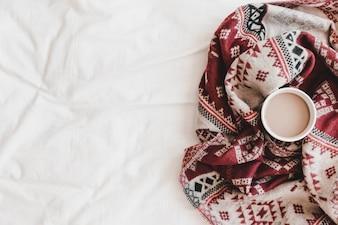 Tasse heißes Getränk in gemusterten Plaid auf Bettlaken