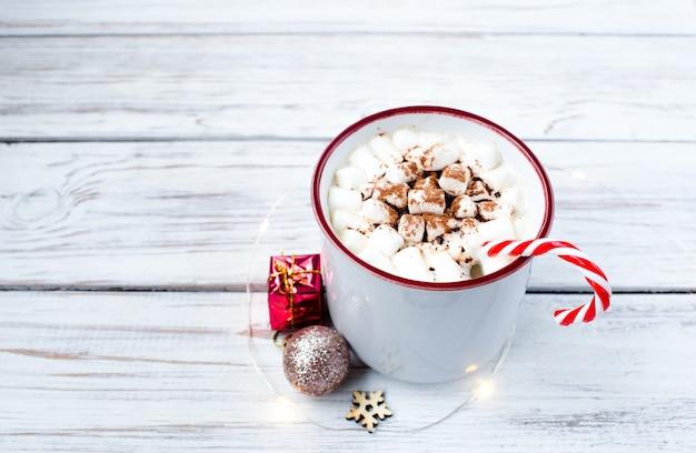 Tasse heißes weihnachtsgetränk auf hölzernen blauen hintergrundweihnachtsgeschenken. die ansicht von der spitze.