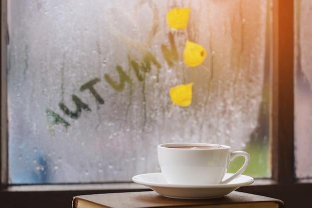 Tasse herbsttee, kaffee, schokolade und gelbe blätter auf regnerischem fenster. heißes getränk für herbststimmung.