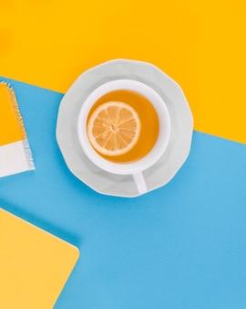 Tasse ingwertee mit zitrone auf gelbem und blauem hintergrund