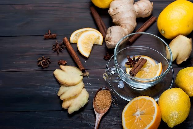 Tasse ingwertee mit zitrone und honig auf dunkelbraunem hölzernem