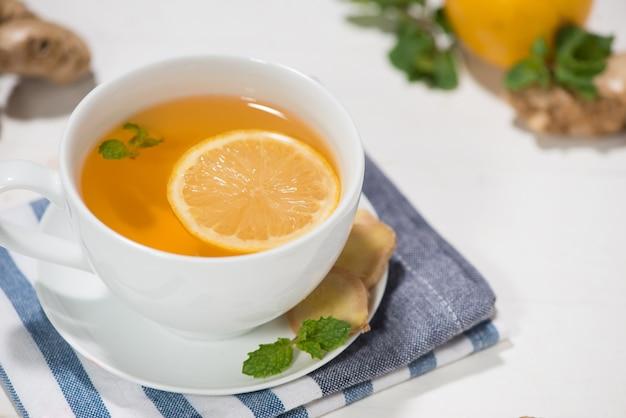 Tasse ingwertee mit zitrone und honig auf weißem hintergrund aus holz.