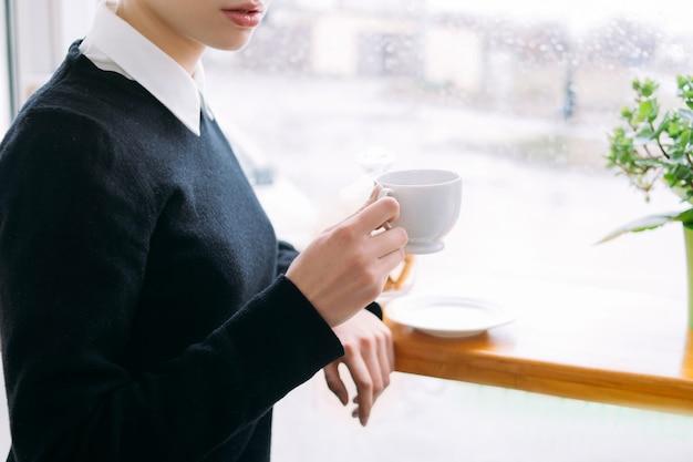 Tasse kaffee am morgen. koffeinabhängigkeit. frau, die eine tasse heißes belebendes getränk hält