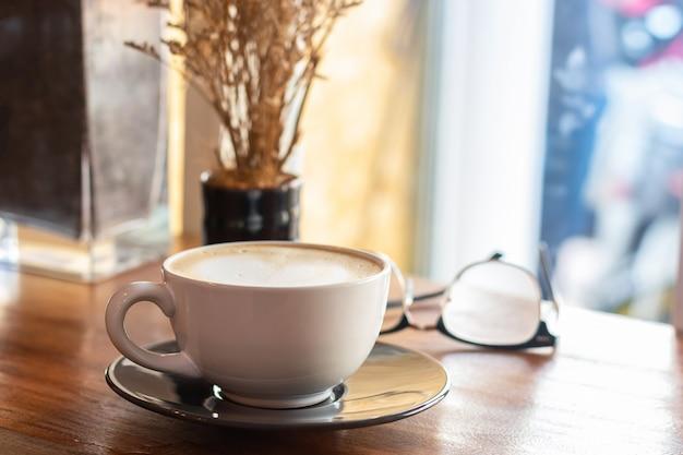 Tasse kaffee auf altem hölzernem schreibtisch