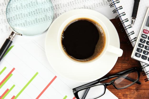Tasse kaffee auf arbeitstisch mit dokumenten nahaufnahme bedeckt
