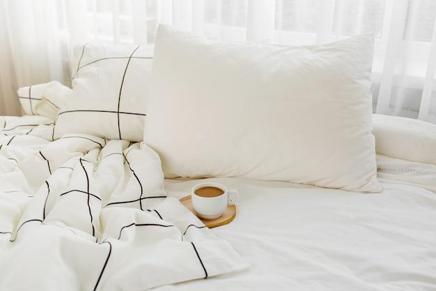 Tasse kaffee auf dem bett. weiße bettwäsche mit gestreifter decke und kissen.