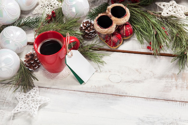 Tasse kaffee auf dem holztisch mit einem leeren leeren preisschild und weihnachtsdekorationen.