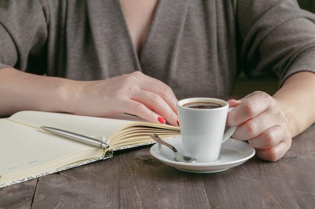 Tasse kaffee auf dem schreibtisch und der frau, die an seinem flachen projekt arbeiten