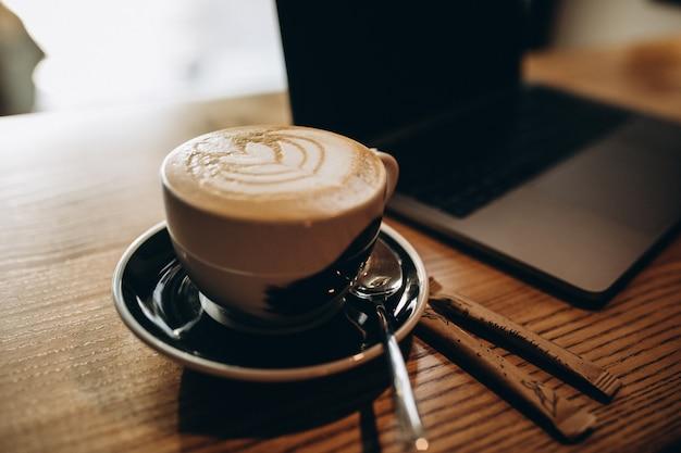 Tasse kaffee auf dem tisch neben dem laptop