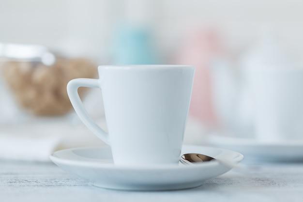 Tasse kaffee auf dem tisch und verschwommene kerzen
